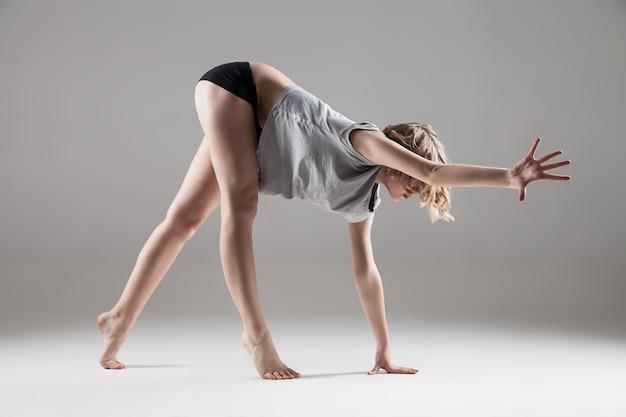Belle jeune femme en t-shirt gris et short noir dansant, série studio