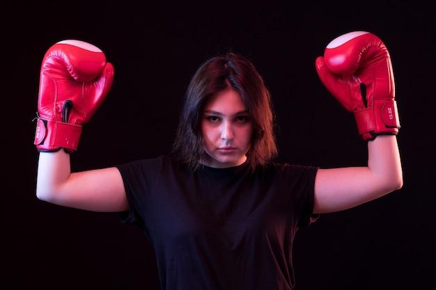 Belle jeune femme en t-shirt noir et gants de boxe rouges