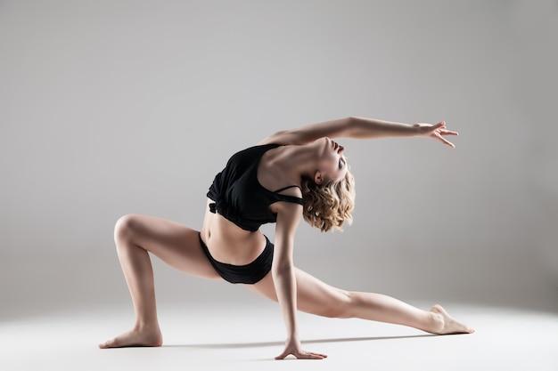 Belle jeune femme en t-shirt noir et short noir dansant, série studio