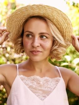 Belle jeune femme avec des taches de rousseur dorées profitant de son temps à l'extérieur dans le parc avec coucher de soleil en arrière-plan.