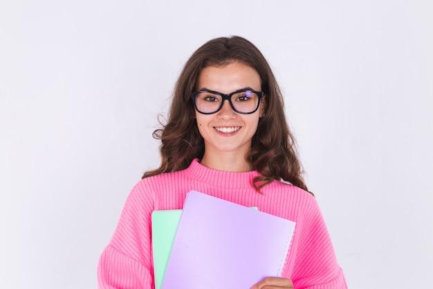 Belle jeune femme avec des taches de rousseur maquillage léger en pull sur mur blanc étudiant à lunettes sourire heureux joyeux positif