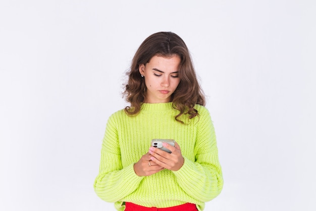 Belle jeune femme avec des taches de rousseur maquillage léger en pull sur mur blanc avec téléphone portable grave triste en colère