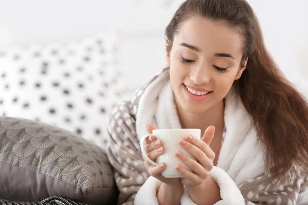 Belle jeune femme avec une tasse de thé chaud à la maison