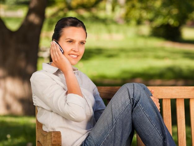 Belle jeune femme téléphonant sur le banc