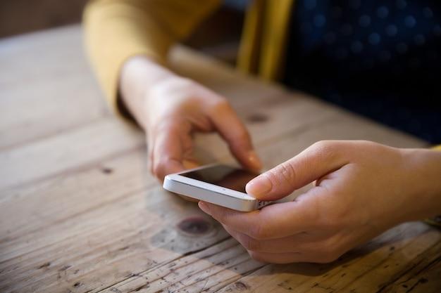 Belle jeune femme avec téléphone portable assise confortablement à une table en bois