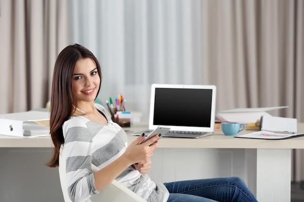 Une belle jeune femme avec un téléphone portable travaillant à la maison en tant que pigiste