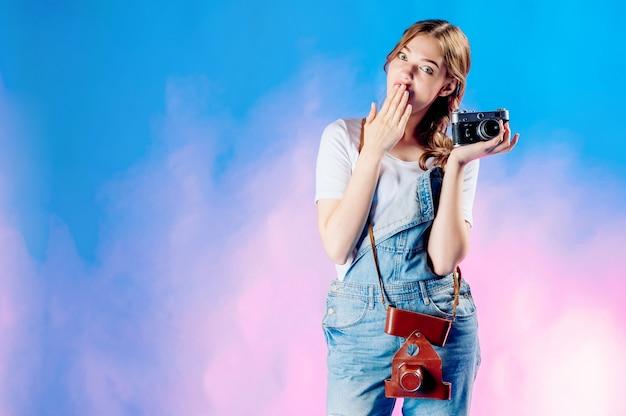 Belle jeune femme tenant un appareil photo rétro va voyager