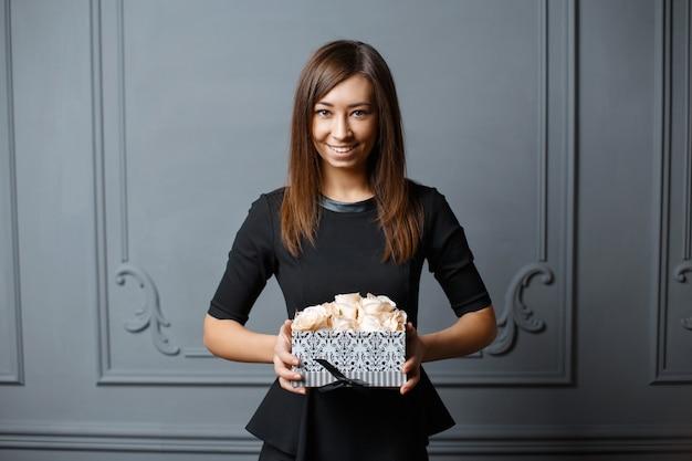 Belle jeune femme tenant une boîte avec des roses blanches.