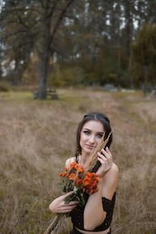 Belle jeune femme tenant un bouquet de fleurs de chrysanthème dans un champ en regardant la caméra