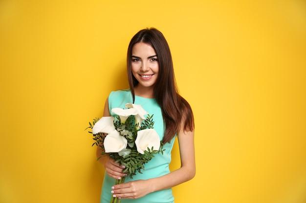 Belle jeune femme tenant un bouquet sur un mur jaune