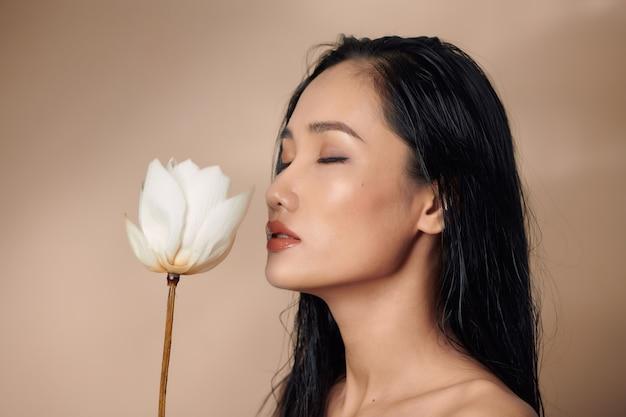 Une belle jeune femme tenant des bourgeons de lotus séchés