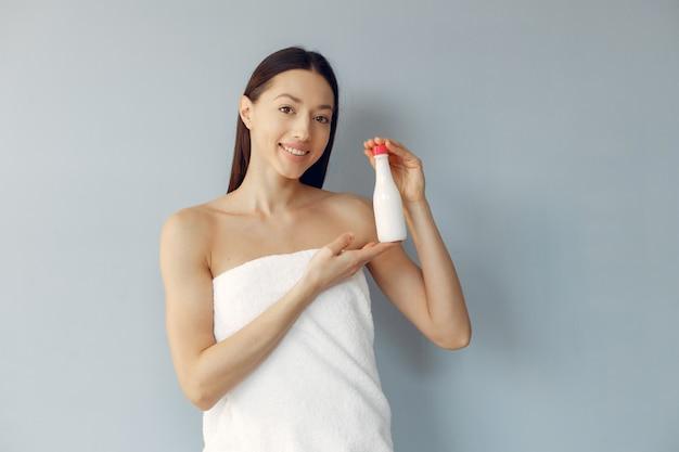 Belle jeune femme tenant une bouteille de crème