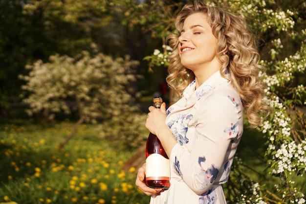 Belle jeune femme tenant une bouteille de vin vierge tout en déjeunant à l'extérieur. pique-nique dans le parc avec de l'herbe verte