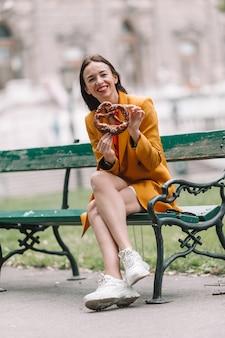 Belle jeune femme tenant un bretzel et se détendre dans le parc