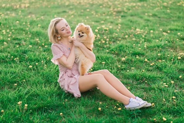 Belle jeune femme tenant un chien spitz à l'extérieur dans le parc.