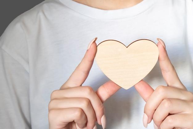 Belle jeune femme tenant un coeur en bois dans les mains. heure d'hiver.