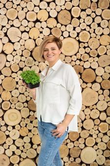 Belle jeune femme tenant une couleur micro-verte sur le d'un mur en rondins de bois.