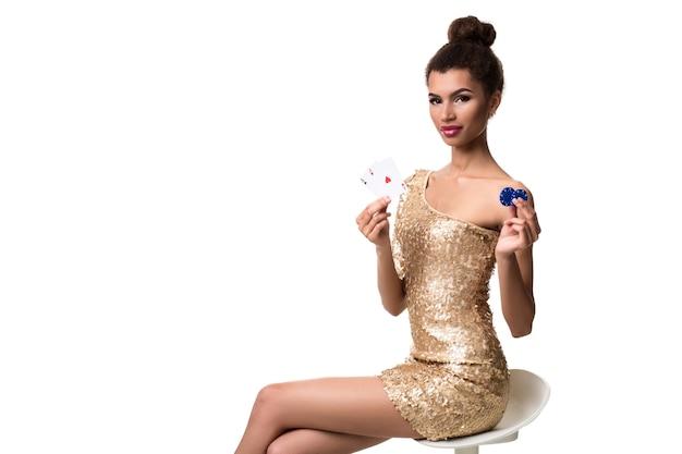 Belle jeune femme tenant deux as de cartes et deux jetons dans sa main isolated on white