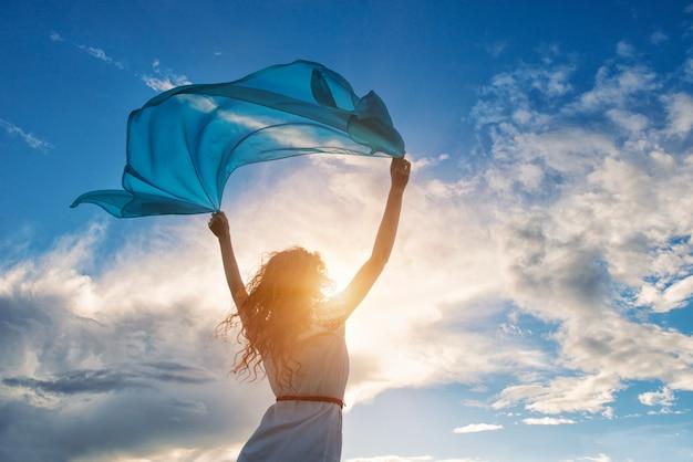 Belle jeune femme tenant une écharpe bleue sur le vent