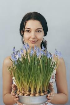 Belle jeune femme tenant des fleurs de printemps en pot de fleurs en regardant l'avant