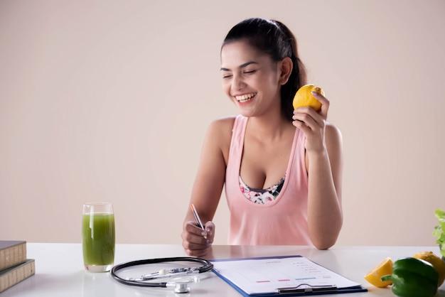 Belle jeune femme tenant des fruits orange dans la main. sourire avec un sentiment heureux. stéthoscope, et, brouillé, régime alimentaire, formulaire, mettre, bureau., femme saine