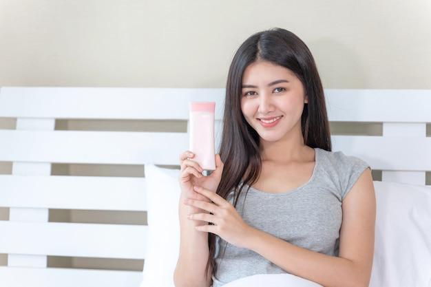 Belle jeune femme tenant et lotion pour la peau dans sa main et souriant avec bonheur