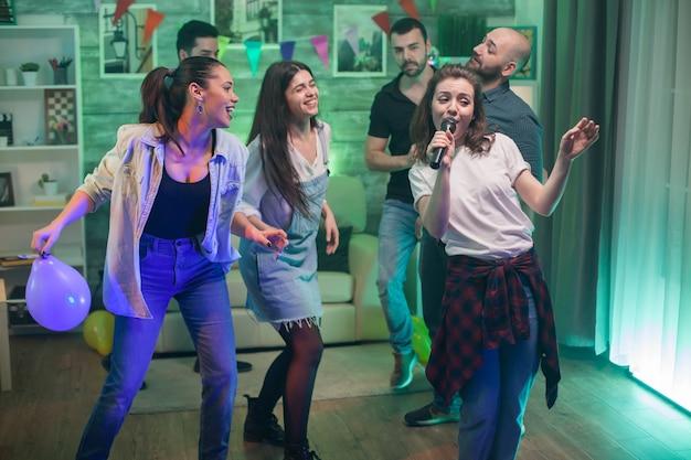 Belle jeune femme tenant le microphone tout en faisant du karaoké avec ses amis.