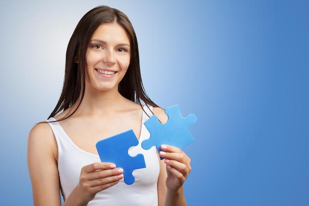 Belle jeune femme tenant un morceau de puzzle