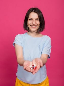Belle jeune femme tenant de nombreuses pilules dans ses mains