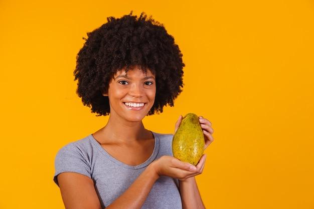 Belle jeune femme tenant la papaye sur jaune