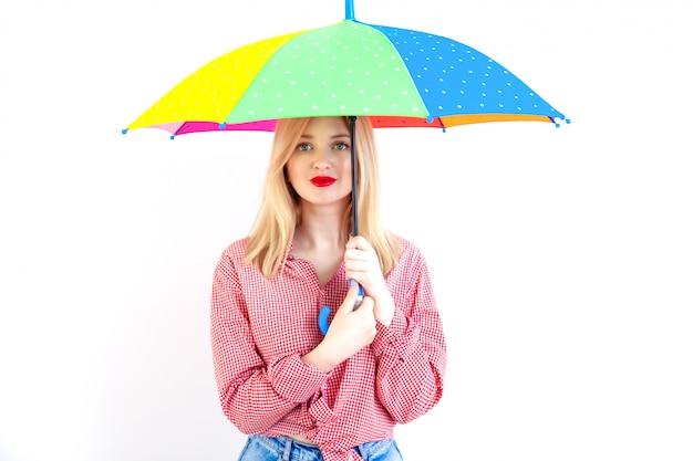 Belle jeune femme tenant un parapluie coloré sur blanc