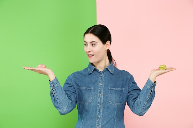 Belle jeune femme tenant la pâte de macarons dans ses mains, plus de couleur tendance au studio.