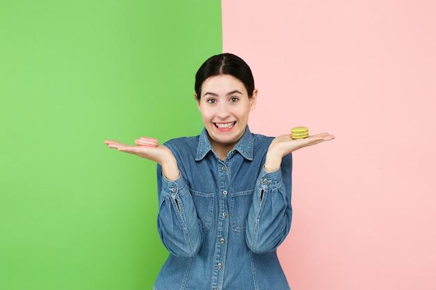 Belle jeune femme tenant la pâtisserie macarons dans ses mains