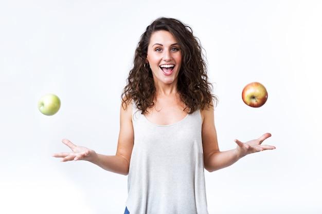 Belle jeune femme tenant des pommes vertes et rouges sur fond blanc.