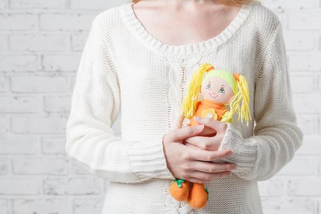 Belle jeune femme tenant une poupée dans le salon près de la fenêtre à la maison. concept de détente en vacances.