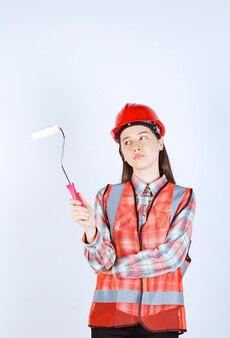 Belle jeune femme tenant un rouleau à peinture pour peindre la réparation du mur.