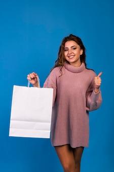 Belle jeune femme tenant un sac en papier blanc blanc et fait des achats dans une boutique en ligne