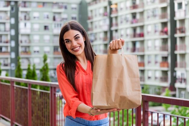 Belle jeune femme tenant un sac en papier à emporter de la livraison