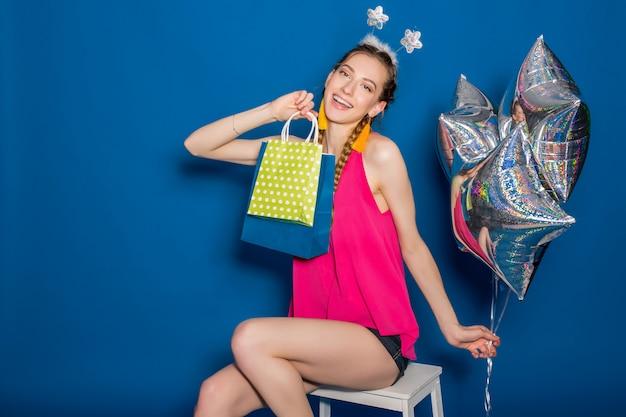 Belle jeune femme tenant des sacs à provisions et des ballons