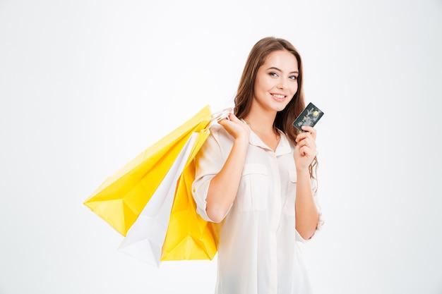 Belle jeune femme tenant des sacs à provisions et une carte de crédit isolée sur un mur blanc