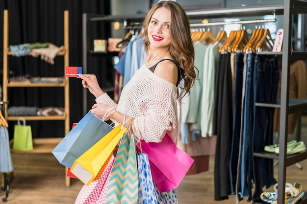 Belle jeune femme tenant des sacs à provisions et une carte de crédit