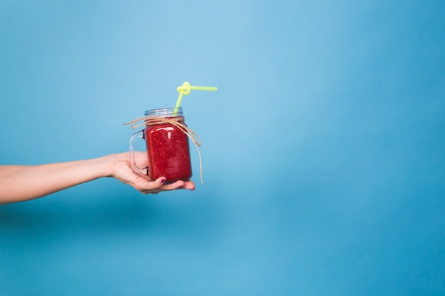 Belle jeune femme tenant un smoothie aux fraises sur bleu. concept de boissons biologiques saines. les gens au régime.