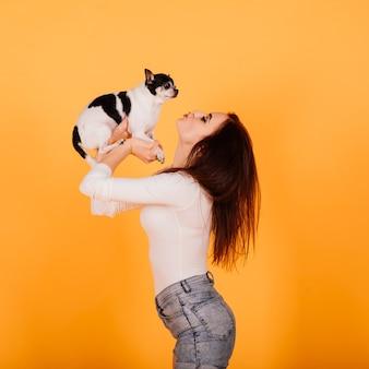 Belle jeune femme tenant son chien sur fond jaune.