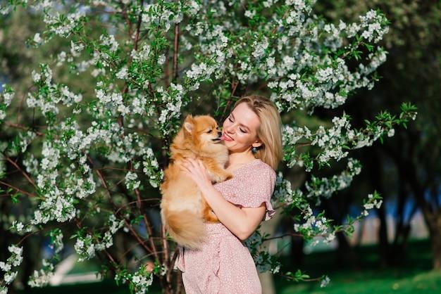 Belle jeune femme tenant un spitz de chien à l'extérieur, marchant dans le parc.