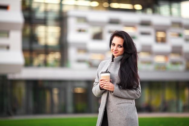Belle jeune femme tenant une tasse de café et souriant en se promenant dans la rue