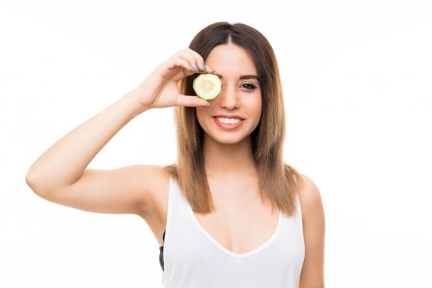 Belle jeune femme tenant des tranches de concombre
