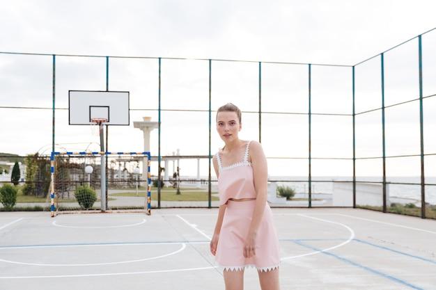 Belle jeune femme tendre debout sur une aire de jeux extérieure