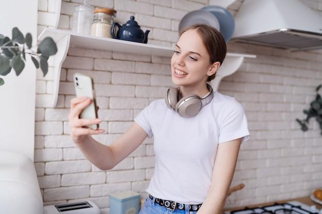 Belle jeune femme en tenue décontractée est assise sur la table de la cuisine avec des écouteurs, faisant un appel vidéo