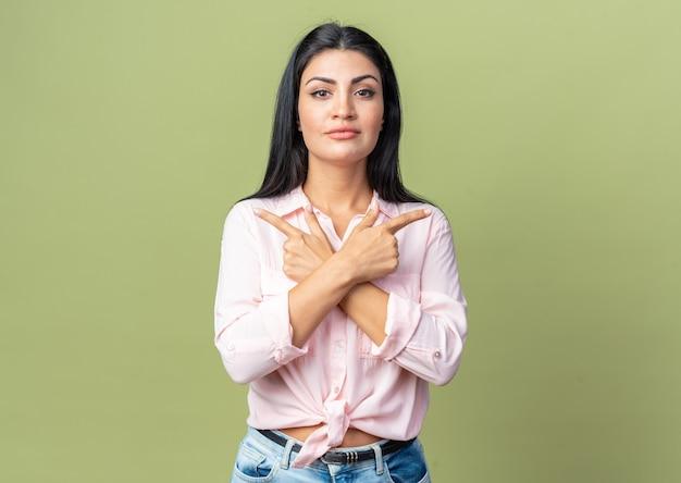 Belle jeune femme en tenue décontractée avec une expression confiante croisant les mains pointant avec l'index vers les différents côtés