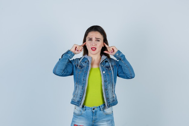 Belle jeune femme en tenue de denim se bouchant les oreilles avec les doigts et ayant l'air ennuyée, vue de face.